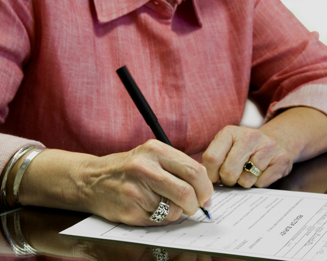female signing a legal document