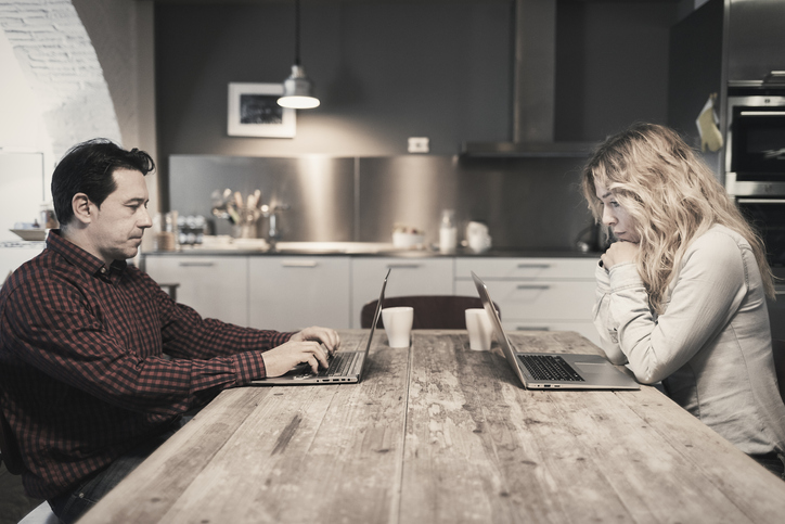 Couple working on laptops at kitchen table